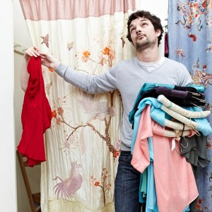 Man holding clothes by a changing room --- Image by © Liam Norris/cultura/Corbis